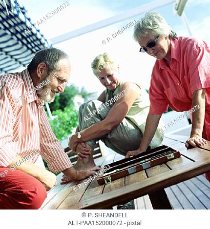 Three mature adults playing backgammon