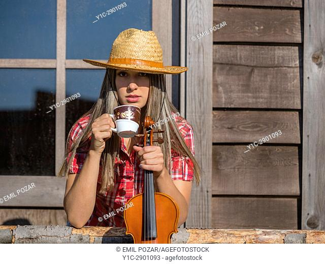 Country-girl countrygirl drinking coffee and violin in hands in wild west environment. Croatia