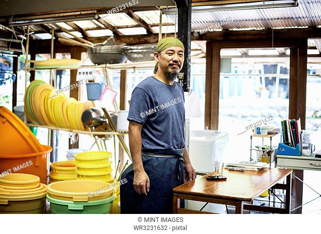 Japanese man wearing bandana standing in a textile plant dye workshop, smiling at camera