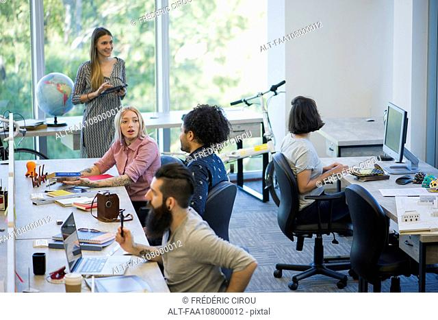 Colleagues sharing ideas in casual office space