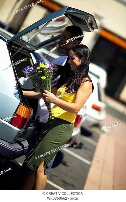 couple stowing in things in their car trunk on a parking lot