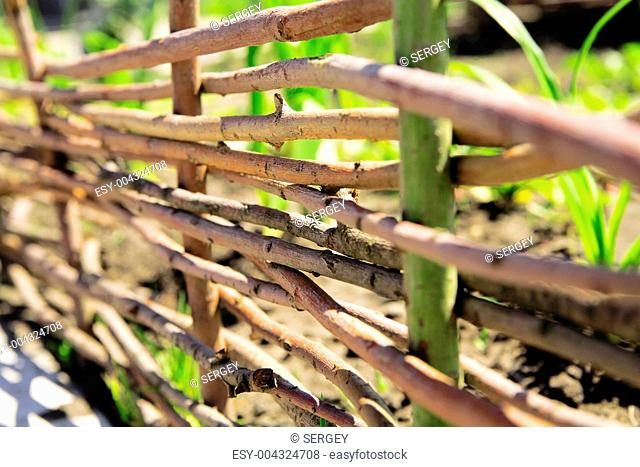 Fence from wooden twigs as a rural background