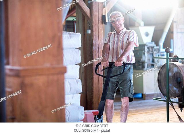 Portrait of male miller using pallet jack to move sacks of flour at wheat mill