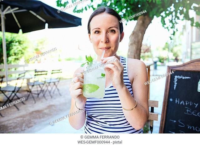 Happy woman drinking homemade lemonade in summer