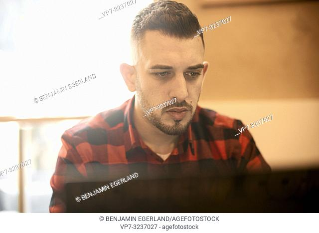 closeup of man working with laptop indoors in café, casual shirt, freelancer, self employee, Greek ethnicity, in Munich, Germany