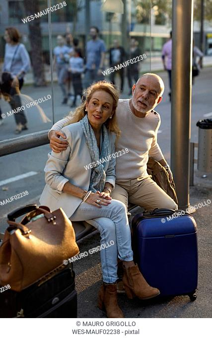 Spain, Barcelona, senior couple with baggage waiting at tram stop in the city