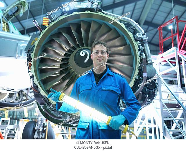 Portrait of engineer in front of jet engine in aircraft maintenance factory