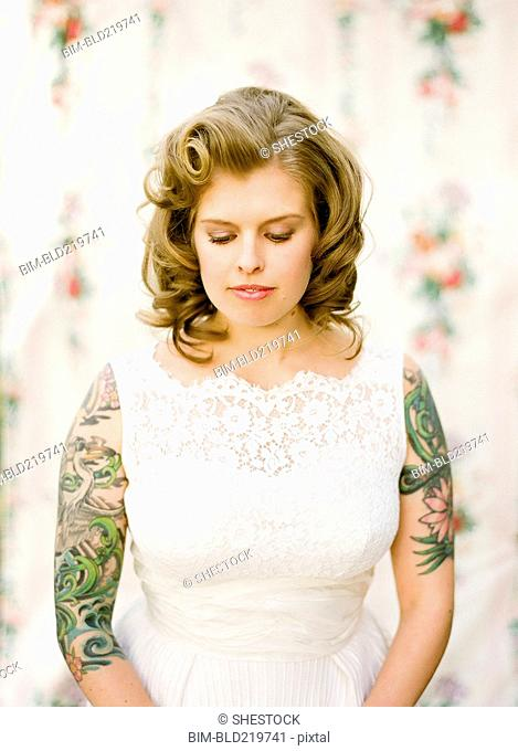 Close up of bride with tattoos wearing wedding dress
