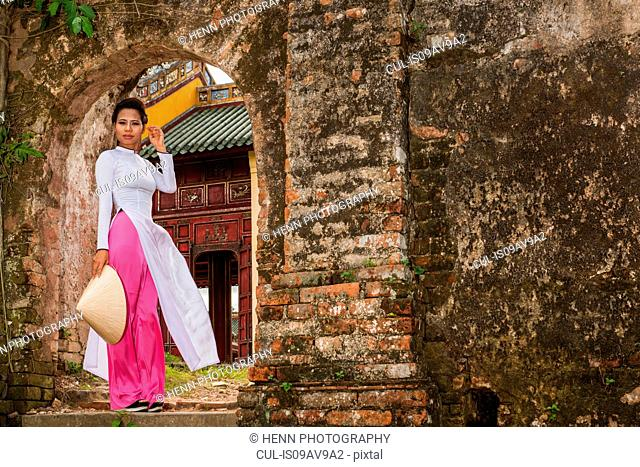 Mid adult woman wearing ao dai dress standing on step holding conical hat looking at camera, Hue, Vietnam