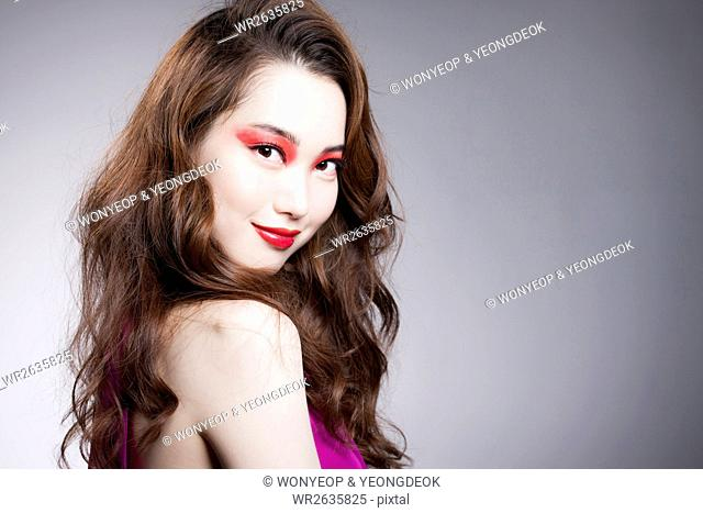 Portrait of young Korean woman in red eye shadow and red lips