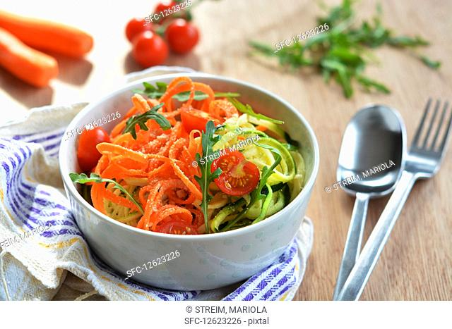 Vegetable spaghetti made with carrots and courgette, fresh tomatoes and rocket