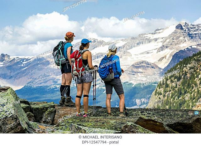 Three female hikers on a mountain rock overlooking mountain vista in the background; British Columbia, Canada