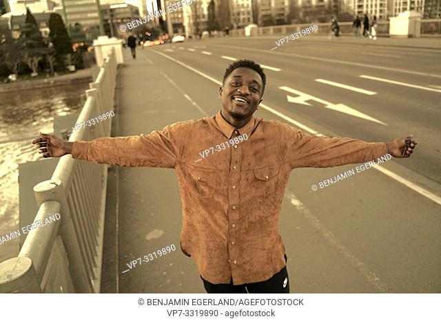 carefree African man with open arms at street in city, in Frankfurt, Germany