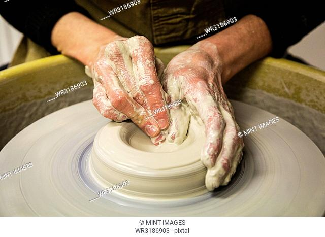 Close up of potter wearing apron working on pottery wheel, shaping clay vase