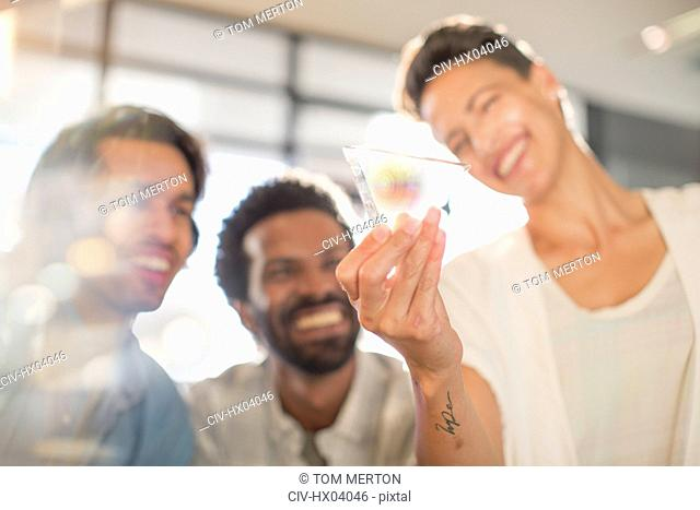 Smiling, curious, innovative entrepreneurs examining glass triangle prototype