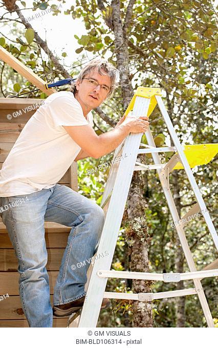 Hispanic man climbing ladder