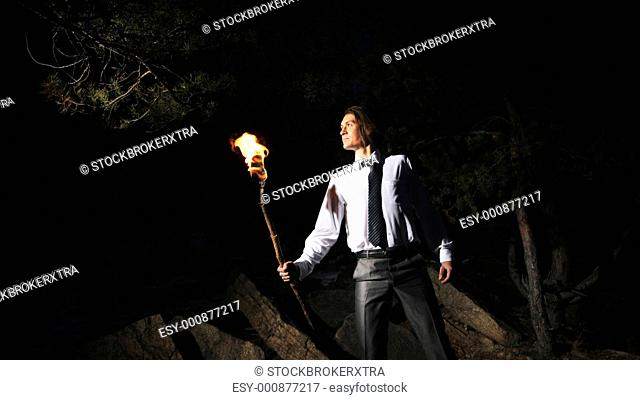 Image of brave man holding burning stick while moving in darkness