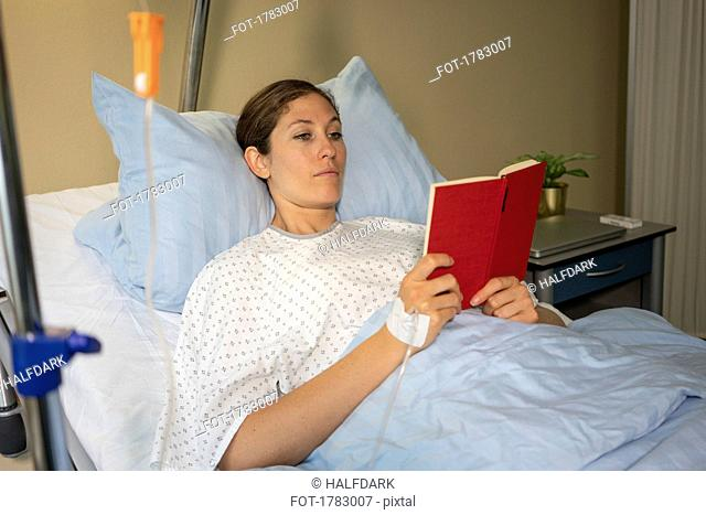 Female patient reading book, resting and recovering in hospital room