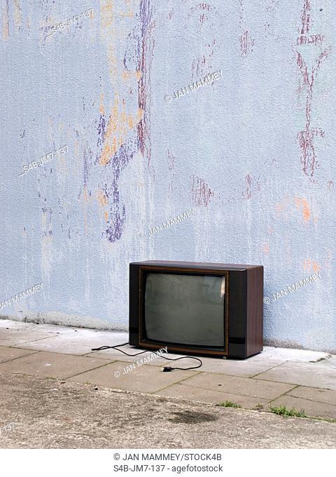 Old television at house wall