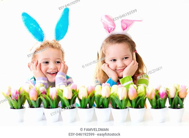 Happy children celebrate Easter at home. Boy and girl wearing bunny ears enjoying egg hunt. Kids playing with color eggs and flower basket