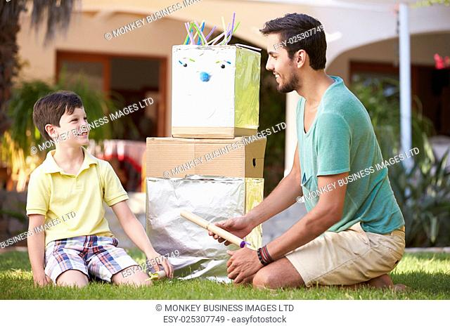 Father And Son Building Model Robot In Garden
