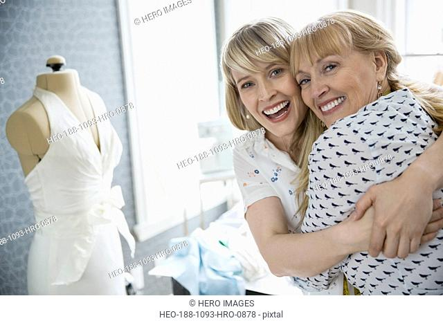 Portrait of seamstress and daughter hugging