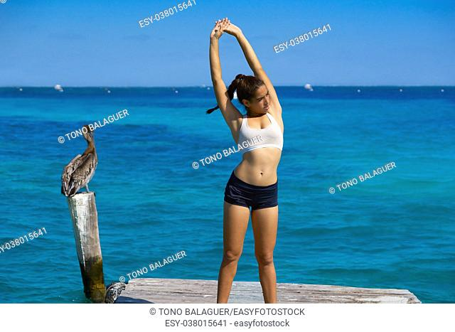 Latin athlete woman stretching in Caribbean beach pier