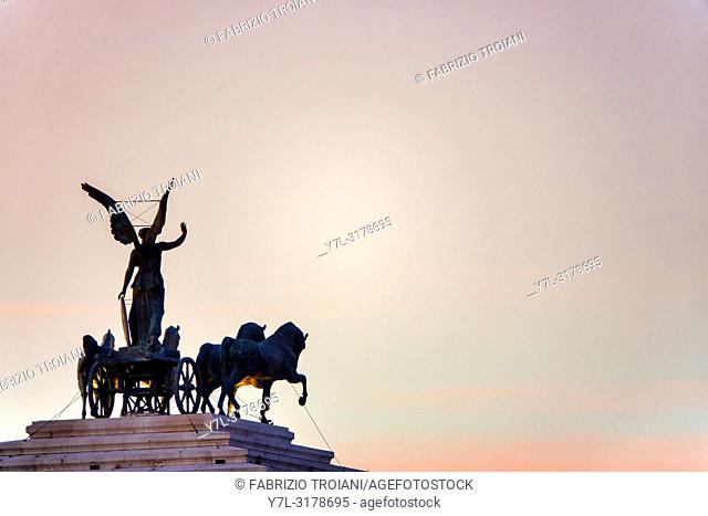 Statue of the goddess Victoria riding on quadriga on the top of the Monument to Vittorio Emanuele II at sunset, Rome, Italy