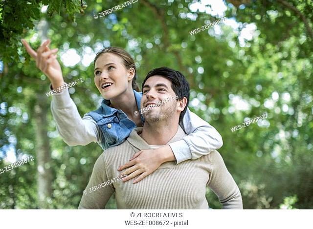 Young man carrying his girfriend piggyback in the nature
