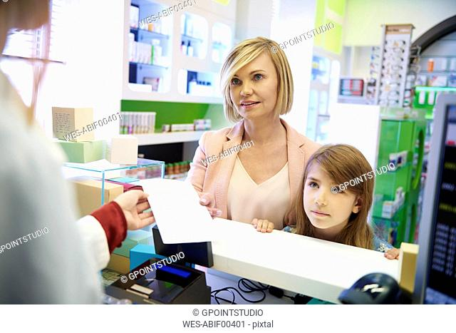 Pharmacist advising woman and child in pharmacy