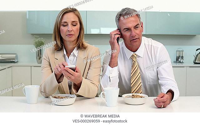 Couple having breakfast and using phones before work