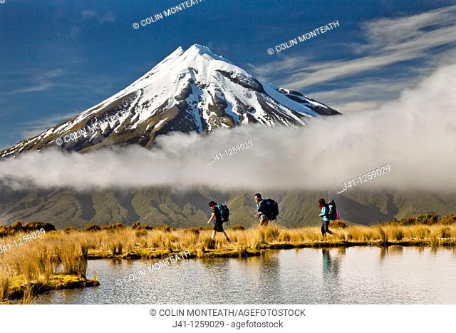 Trampers under Mt Egmont / Taranaki, reflection in small tarn set among tussock slopes of Pouakai range, Taranaki