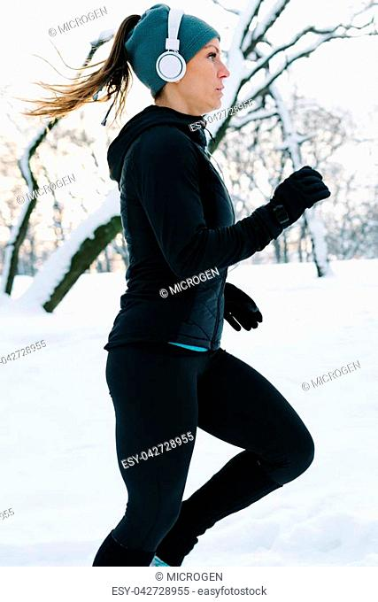Female athlete jogging in park in winter with snow around the park. Listeninig music and exercising