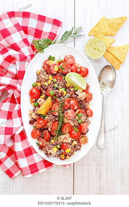 Mixed Mexican quinoa salad with lime dressing on white plate, ready to eat. Natural light
