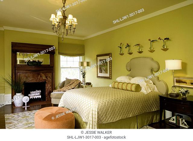 BEDROOM: citron color, antique fireplace mantel with coral marble, contemporary floral in front of mirror, tangerine and coral accents, upholstered headboard