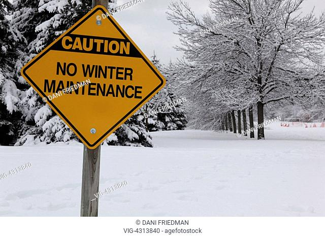 No winter maintenance sign in front of snow covered trees after a fresh snowfall in Markham, Ontario, Canada. - MARKHAM, ONTARIO, Canada, 02/02/2014