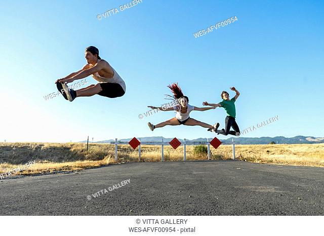 Three acrobats jumping mid-air