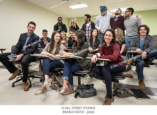 Professor and students smiling in college classroom