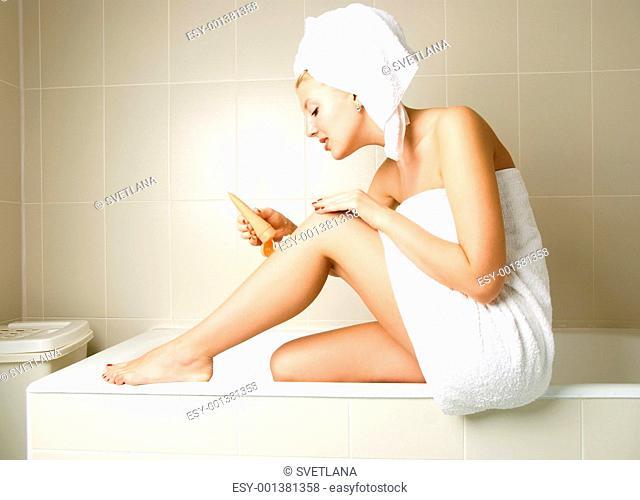 pretty girl applying body lotion