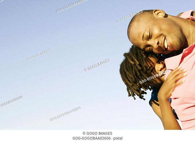 African father carrying his daughter on his shoulders