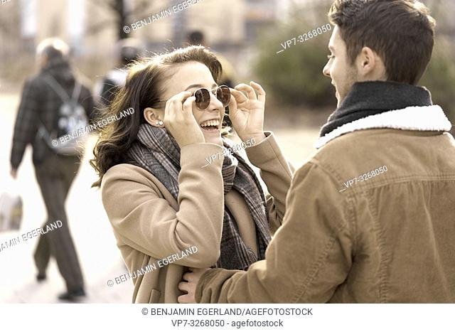 enthusiastic teenage woman touching sunglasses while looking at boyfriend, in Cottbus, Brandenburg, Germany