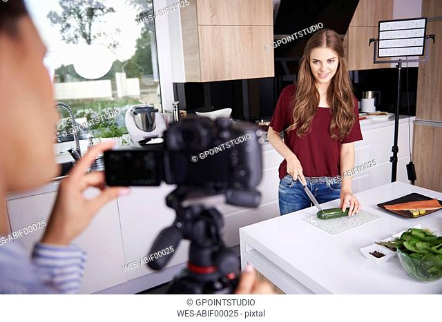 Woman recording her friend while chopping a courgette