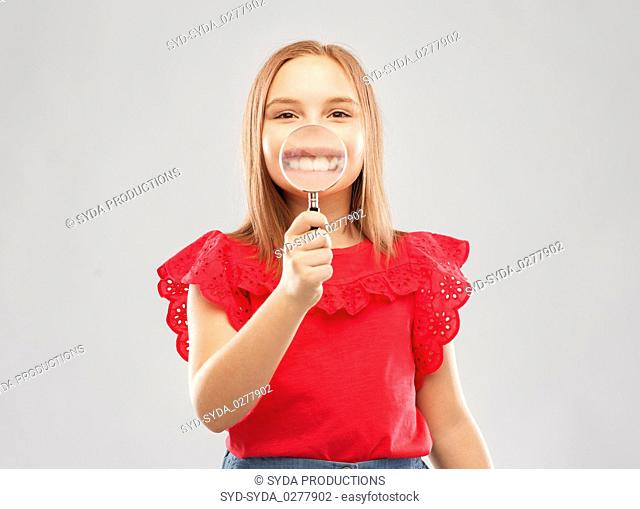 happy girl with magnifying glass over her teeth