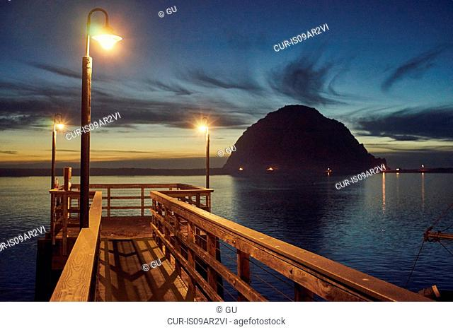 Silhouetted view of Morro Bay Rock and pier at dusk, Morro Bay, California, USA
