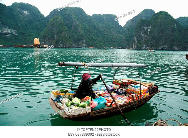 Vietnamese goods and snack seller on floating market-woman selling goods and snack from her boat in the Halong Bay in Quang Ninh, Vietnam