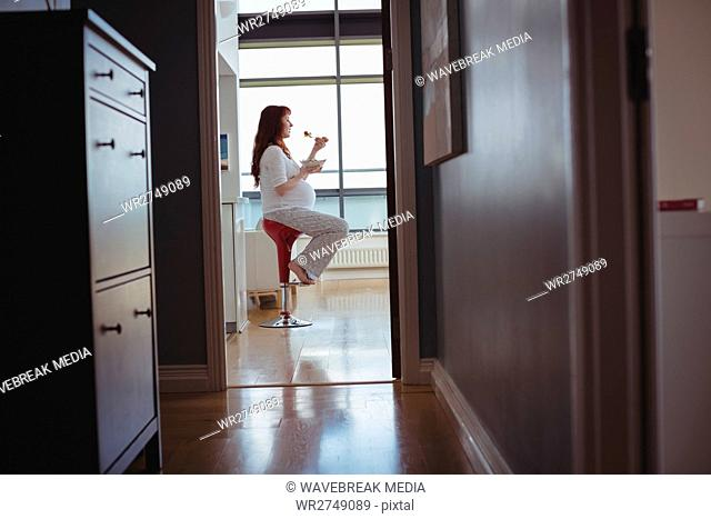 Pregnant woman sitting on stool and eating salad