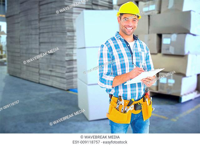 Composite image of portrait of smiling handyman writing on clipboard