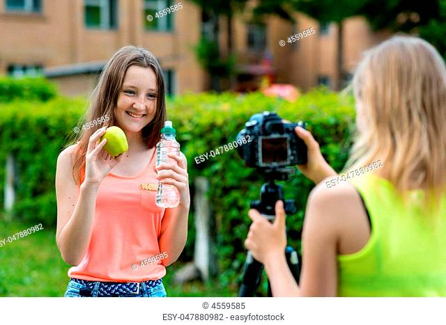 Two girls in the summer in nature. They talk about healthy eating. In hands of an apple a bottle of water. Smiles happily