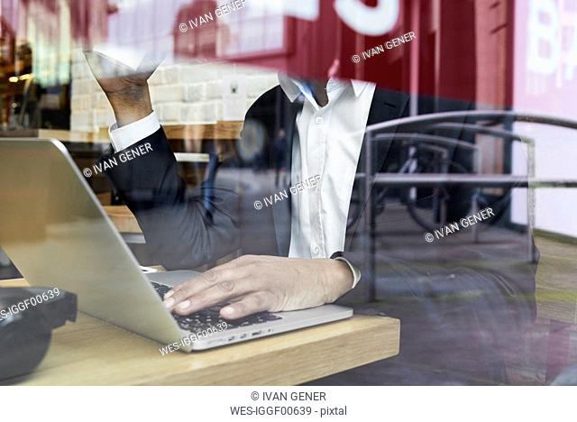 Senior businessman behind windowpane in a coffee shop working on laptop