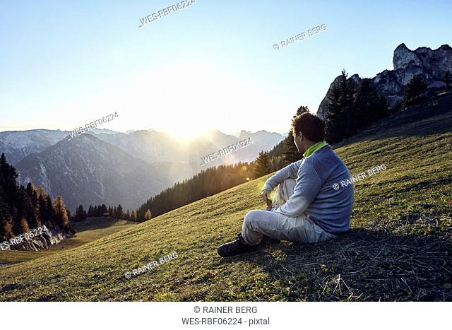 Austria, Tyrol, Rofan Mountains, hiker sitting on meadow at sunset
